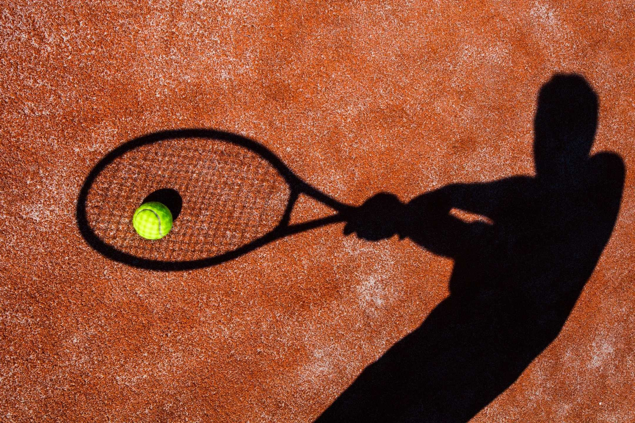 Schatten von Tennisspieler auf Tennisplatz mit Tennisball